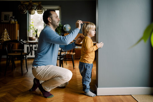 Full length of father measuring daughter's height against wall at home - MASF11614