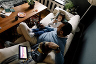 High angle view of father and daughters using various technologies on couch in living room at home - MASF11617