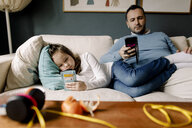 Father and daughter using mobile phones on couch in living room - MASF11620