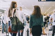 Rear view of young businesswoman talking with female colleague while walking at airport - MASF11629