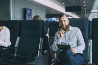Portrait of businessman sitting with digital tablet in waiting room at airport departure area - MASF11659