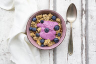 Granola with blueberries and blueberry yoghurt in bowl on white wood - LVF07883