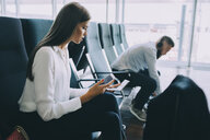 Young businesswoman holding smart phone and passport while sitting at waiting area in airport - MASF11665