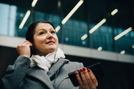 Low angle view of smiling businesswoman listening music while standing against building in city - MASF11746