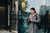 Businesswoman using smart phone while standing against building in city - MASF11764