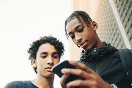 Low angle view of teenage boy showing mobile phone to friend in city - MASF11776