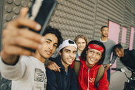 Happy male friends taking selfie with smart phone in city - MASF11824