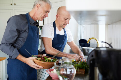 Mature men talking while cooking food in kitchen at home - MASF11842
