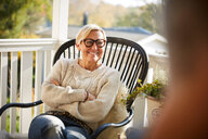 Cheerful mature woman with arms crossed looking away while sitting on porch - MASF11848