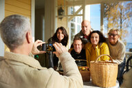 Mature man photographing friends with smart phone on porch - MASF11854