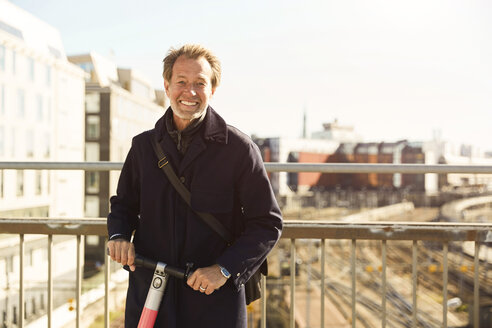 Portrait of smiling mature man standing with electric push scooter on bridge against sky in city - MASF11863
