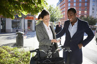 Smiling woman showing smart phone to man while standing with electric bicycle in city - MASF11872