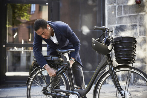Young male commuter locking electric bicycle against building in city - MASF11878