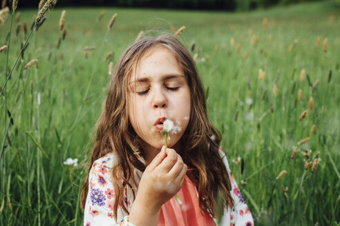 Portrait of girl blowing blowball on a meadow - ANHF00099