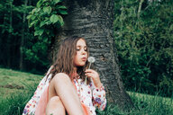 Portrait of girl sitting on a meadow blowing blowball - ANHF00105