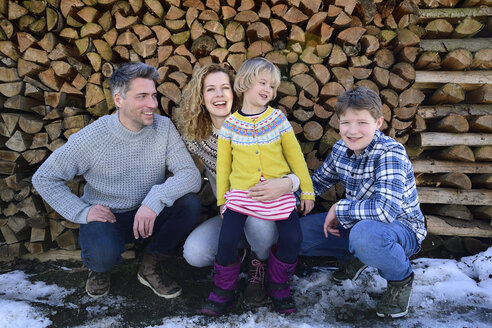 Portrait of happy family in front of stack of wood in winter - ECPF00600