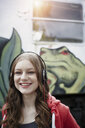 Portrait of happy teenage girl wearing headphones at a painted train car - RORF01813