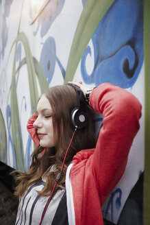 Portrait of teenage girl wearing headphones at a painted train car - RORF01816