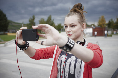 Teenage girl taking a selfie at a skatepark - RORF01834