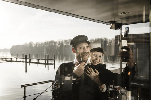 Colleagues working on a houseboat, taking selfies as sailor and captain - MJRF00084