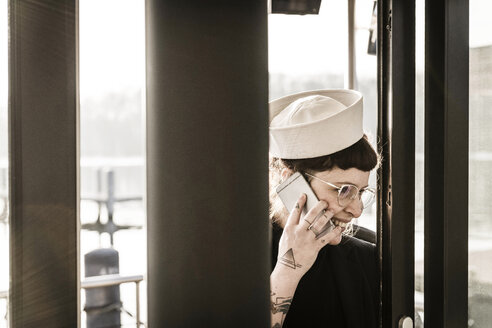 Woman with a sailor's hat using smartphone on a houseboat - MJRF00087