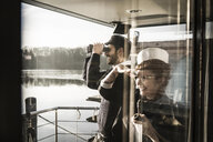 Colleagues working on a houseboat, watching surroundings with binoculars - MJRF00096