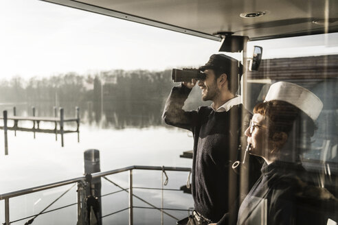 Colleagues working on a houseboat, watching surroundings with binoculars - MJRF00099