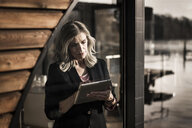 Businesswoman standing on a houseboat, using digital tabet - MJRF00102