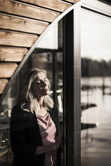 Businesswoman standing on a houseboat,enjoying the sun at the window with eyes closed - MJRF00120