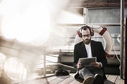 Hip businessman working on a houseboat, using headphones and digital tablet - MJRF00132