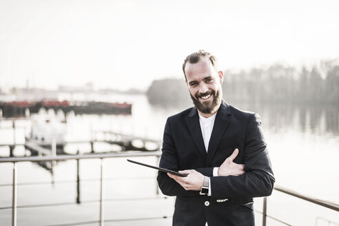Laughing businessman standing on a houseboat, holding digital tablet - MJRF00135