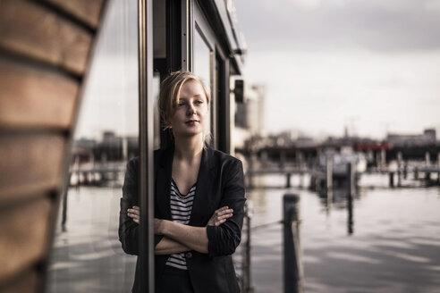 Woman leaning in window of a houseboat, taking a break - MJRF00144