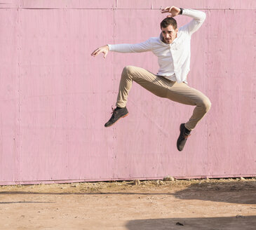 Exuberant young man jumping in front of pink wall - UUF16750