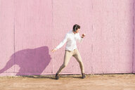 Exuberant young man listening to music in front of pink wall - UUF16753