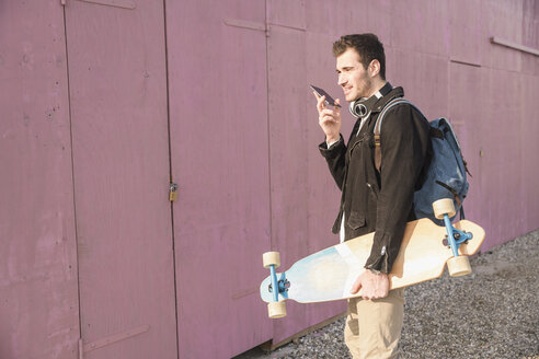 Young man with skatebaord and cell phone on the move - UUF16762