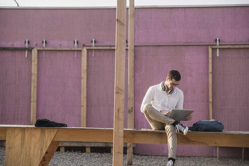 Young man sitting on platform using tablet - UUF16768