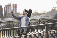 Young man with guitar case and skateboard taking a selfie in the city - UUF16792