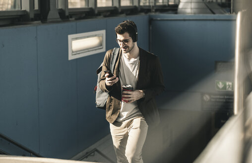 Smiling young man with headphones, cell phone and takeaway coffee walking at the station - UUF16810