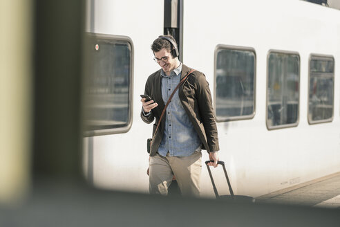 Smiling young man with headphones, cell phone and suitcase walking at station platform - UUF16819