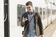 Smiling young man with cell phone at station platform - UUF16822