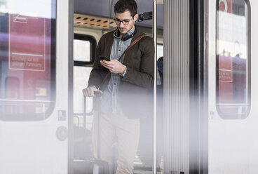 Young man using cell phone in commuter train - UUF16825