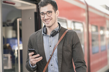 Smiling young man with cell phone at commuter train - UUF16828