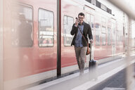 Happy young man with cell phone walking on station platform along commuter train - UUF16831