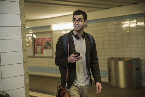 Smiling young man with cell phone walking at station underpass - UUF16837