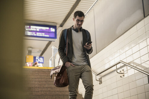 Young man with cell phone walking down stairs at the station - UUF16840
