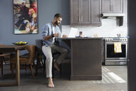 Barefoot man drinking coffee and working at laptop in kitchen - HEROF30149