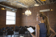 Ambitious businesswoman with digital tablet in conference room with chandelier - HEROF30155