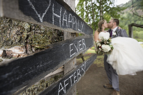 Affectionate bride and groom kissing next to Happily Ever After sign - HEROF30179