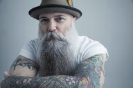 Portrait Caucasian male hipster with long gray beard and arm tattoos wearing fedora - HEROF30184