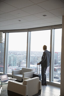 Pensive businessman with suitcase at window in highrise lounge, looking at view - HEROF30259